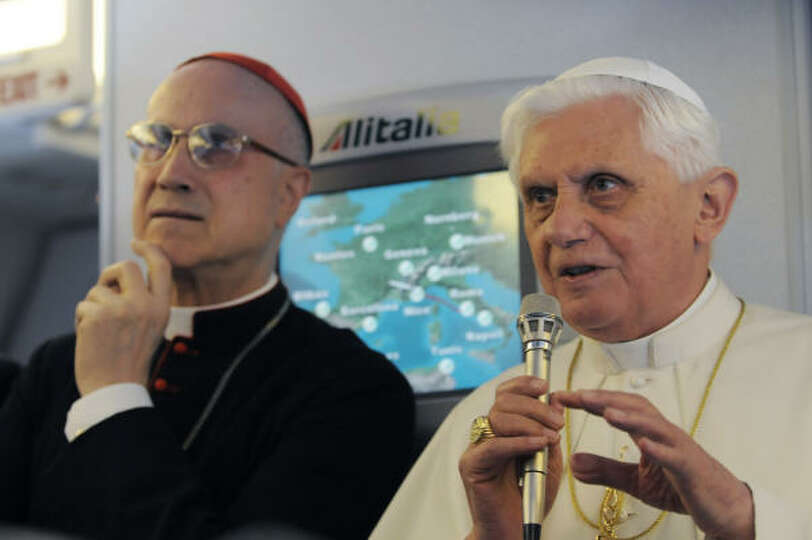 Pope Benedict XVI (R) speaks to reporters accompanying him aboard his flight to the United States on