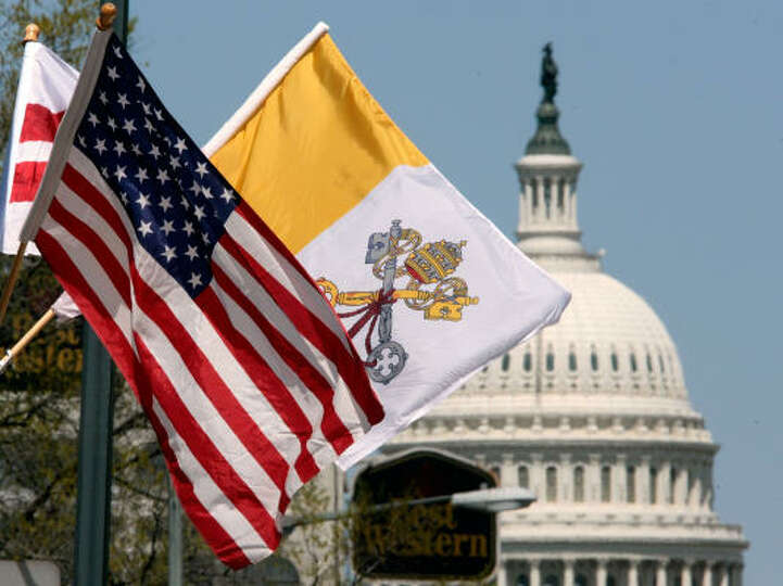 The United States flag and the flag of the Vatican fly side-by-side along South Capitol Street on Tu