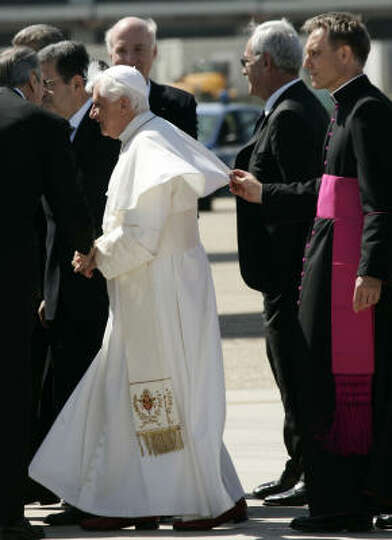 Monsignor Georg Gaenswein, right, holds Pope Benedict XVI's robe, at left, prior to boarding a plane