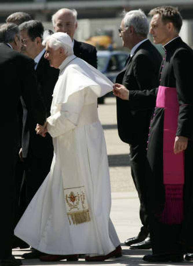 Monsignor Georg Gaenswein, right, holds Pope Benedict XVI's robe, at left, prior to boarding a plane bound for Washington, at Rome's Fiumicino international airport on Tuesday. Benedict departed for Washington on Tuesday, with President Bush planning to make the unusual gesture of greeting him when his special Alitalia jetliner touches down at Andrews Air Force Base. Photo: PLINIO LEPRI, AP