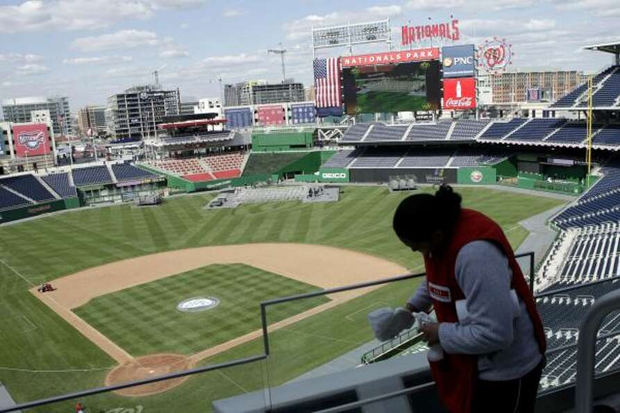 Lorena Gonzalez of Silver Spring, Md., cleans the seating area in the upper deck on Monday as prepar