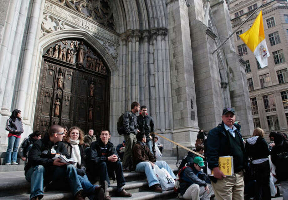 Students in New York on Monday sit on the steps in front of St. Patrick's Cathedral in advance of Pope Benedict's upcoming visit.  The leader of the world's Catholics is scheduled to visit the cathedral during his U.S. visit this weekend. Photo: Chris Hondros, Getty Images