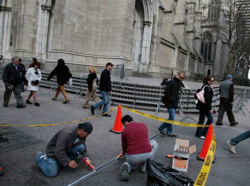 Workers in New York CIty on Monday apply sidewalk grout in front of St. Patrick's Cathedral in advan