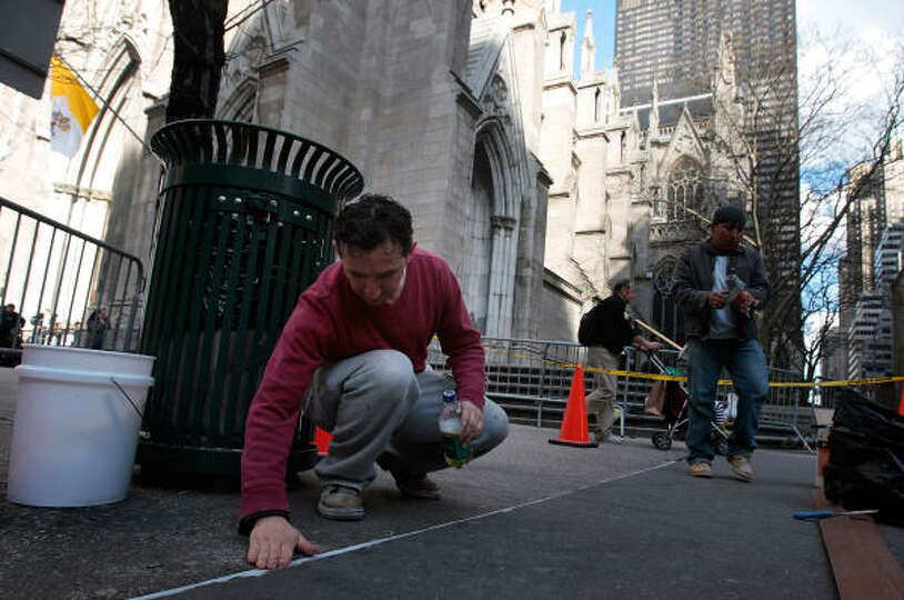 Workers in New York City on Monday smooth sidewalk grout in front of St. Patrick's Cathedral in adva