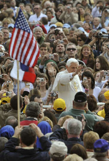 Pope Benedict XVI blesses the faithful as he passes by an USA flag during his weekly general audienc