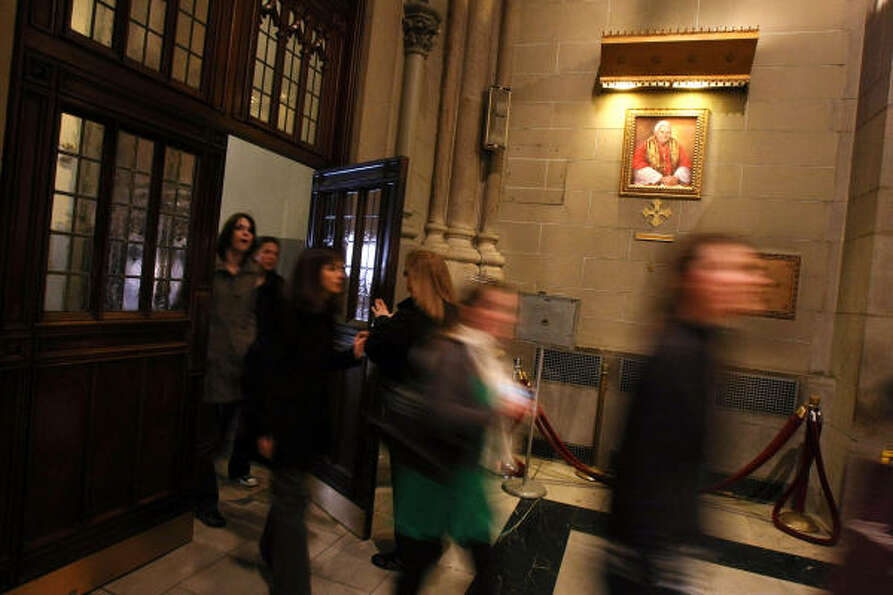 A portrait of Pope Benedict XVI hangs near the entrance as people enter Saint Patrick's Cathedral in