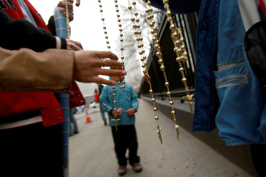 A man peruses crucifixes for sale before the arrival of Pope Benedict XVI for a prayer service with family members of some of those who were killed on Sept. 11 at Ground Zero on Sunday. The Pontiff will conclude his U.S. visit with a Mass in Yankee Stadium later in the day. Photo: Spencer Platt, Getty Images