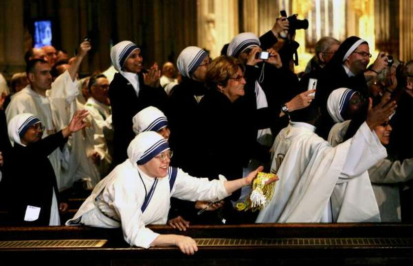 Nuns and other guests inside St. Patrick's Cathedral take photos and greet Pope Benedict XVI as he e