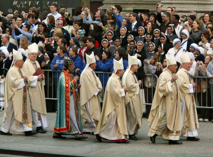 Priest arrive to attend the Mass of Pope Benedict XVI at St. Patrick's Cathedral on Saturday in New