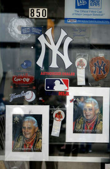 Pope Benedict XVI buttons and posters sit side-by-side with Yankess stickers in the front window at