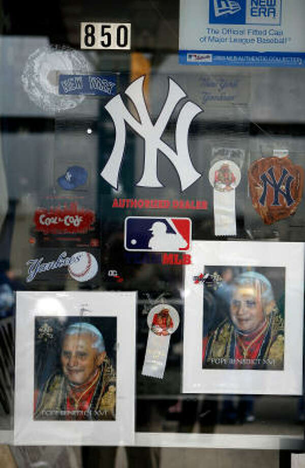 Pope Benedict XVI buttons and posters sit side-by-side with Yankess stickers in the front window at Stan's Sporting Goods across the street from Yankee Stadium where Pope Benedict XVI celebrates Mass on Sunday. Photo: Chip Somodevilla, Getty Images