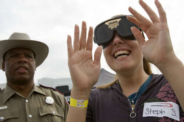 State Trooper John Sampa, left, keeps an eye on Stephanie Smith, 18, as she goes through a simulated sobriety test wearing Fatal Vision goggles at a Driver's Edge seminar at Reliant Park on Sunday in Houston. The goggles simulate perception under the effects of alcohol or drugs.