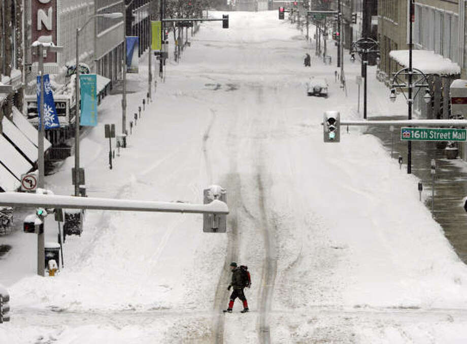 A lone pedestrian ignores the traffic light in downtown Denver. More than 2 feet of snow fell on some parts of Colorado this week before a blizzard moved out of the West. Photo: David Zalubowski, AP