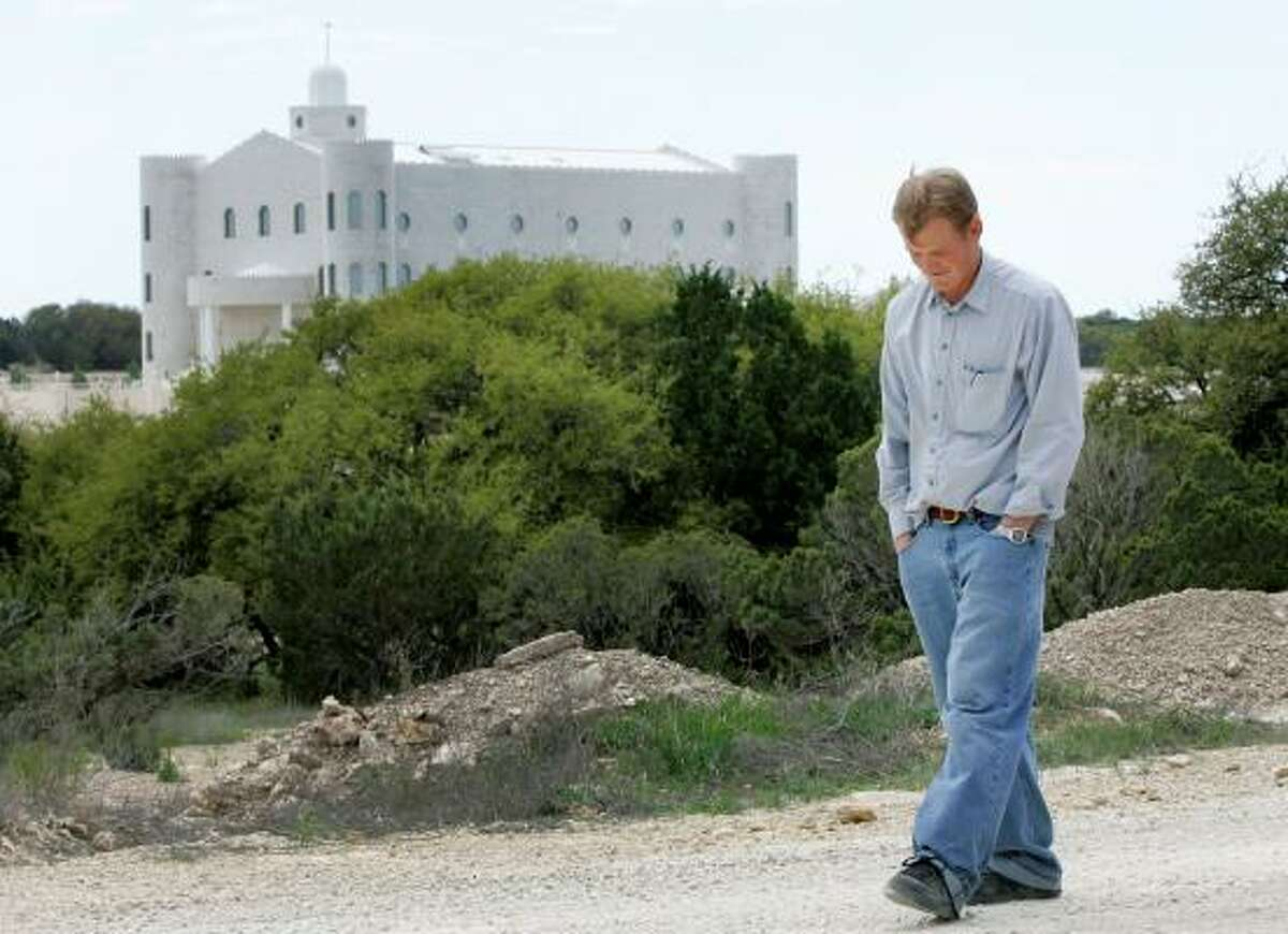 """Dan, 24, a member of the Fundamentalist Church of Jesus Christ of Latter Day Saints walks down a gravel road as he gives journalists a tour of the Yearning For Zion ranch on April 16. Dan, a father of two children currently in state custody, said, """"It is lifeless without our kids around here"""" as the main temple on the ranch is seen at rear."""