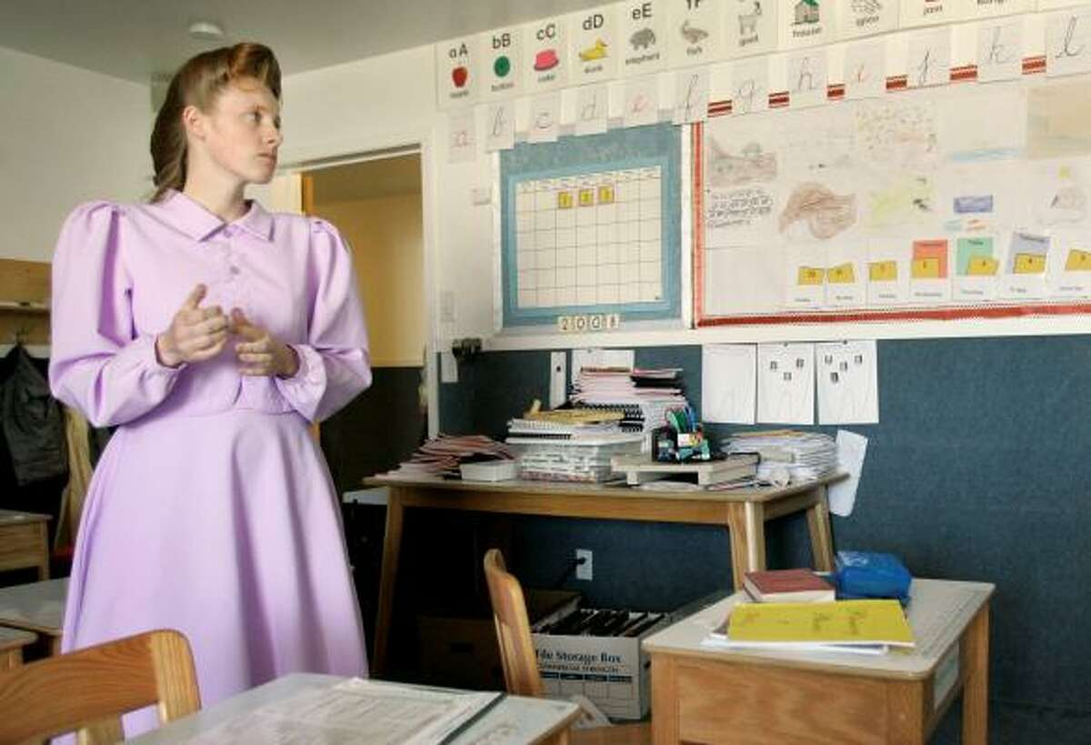 Rozie, 23, a member of the Fundamentalist Church of Jesus Christ of Latter Day Saints stands in a classroom at the school on the ranch.