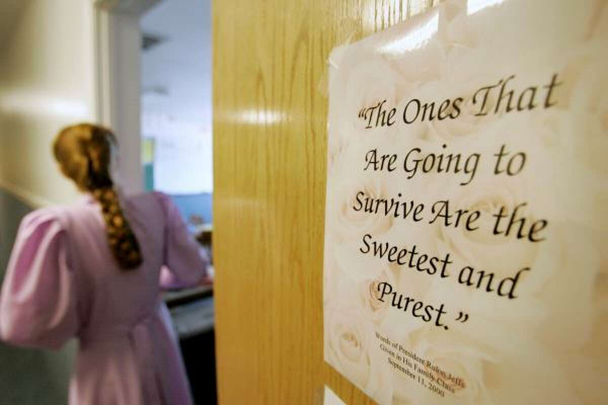 Rozie, 23, walks out of a classroom in the school on the ranch as a sign placed on the door quotes sect leader Rulon Jeffs on April 16