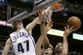 Rockets forward Luis Scola, center, has his shot blocked by Jazz forwards Andrei Kirilenko (47) and Carlos Boozer during the first quarter on Monday.
