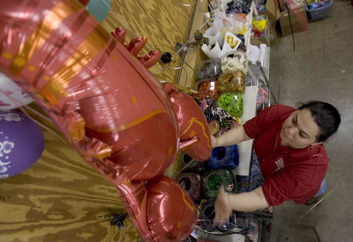 Claudia Hernandez fills a large balloon with helium for a balloon bouquet at Arne's Warehouse Store, one of Houston's largest party suppliers. Amid reports of a helium shortage, the store says it has not experienced any problems.
