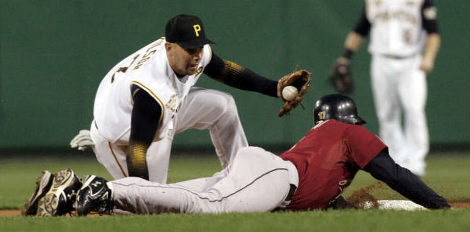 Lance Berkman dives back to second as Pirates shortstop Jack Wilson tries to tag him out in the first inning. Photo: KEITH SRAKOCIC, AP
