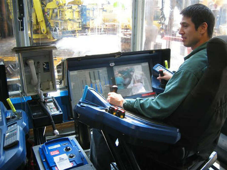 Dan Jovanovic of Houston, drill site manager at Chevron's $2.3 billion Benguela Belize platform off the coast of Angola, controls drilling with two joysticks on a $300 million console. Photo: MICHELLE FAUL, AP