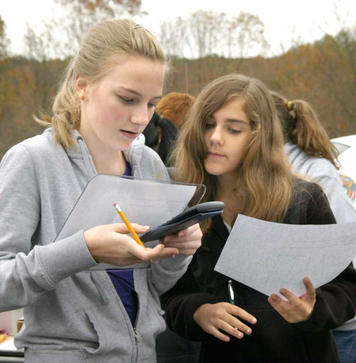 Lauren Lempereur, left and Paige Piera, both 12, calculate an equation of distance = rate x time of a moving car. The girls are seventh grader students in teacher Alison Salerno's pre-algebra class at the Bethel Middle School. Photo taken Oct. 13, 2009