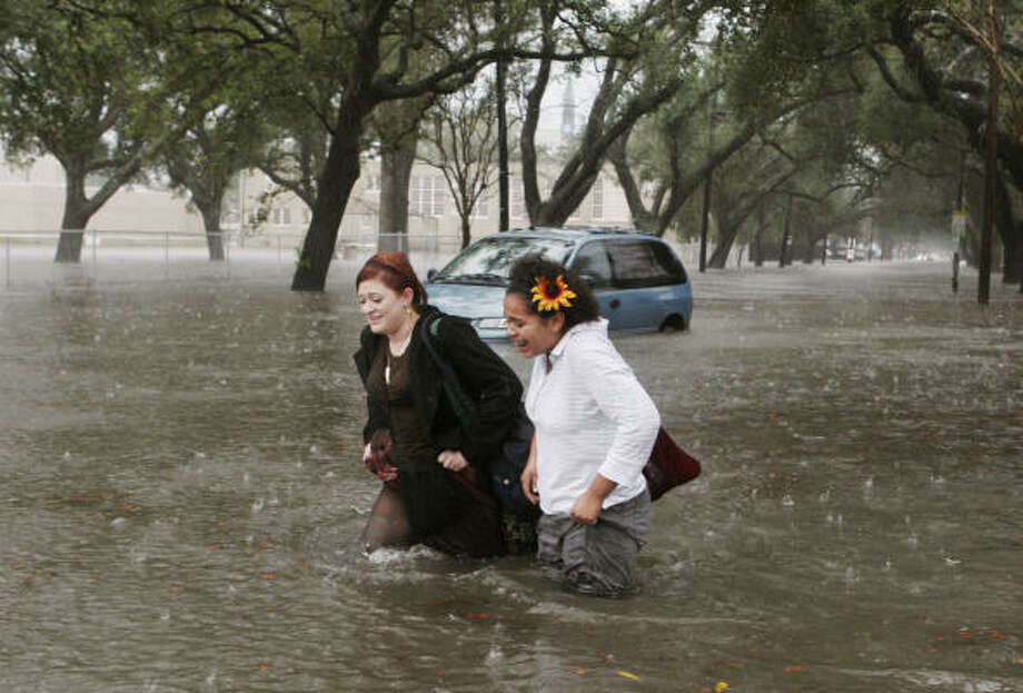 Alison Mantilla, left, and McNally Sislo wade through high water in the Uptown area of New Orleans on Thursday. The National Weather Service issued a flash flood watch until noon today for parts of Louisiana. Photo: Alex Brandon, AP