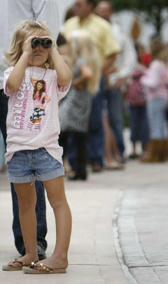Tori Lynn Harris uses her binoculars while waiting in line for the gates to open. Photo: Karen Warren, Chronicle