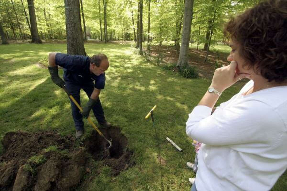 Shannon Kelley watches James P. Gates dig to find the septic tank in her La Plata, Md., yard. As more urbanites move to rural settings, some don't realize their house may have a septic system.