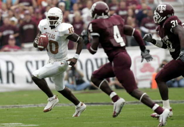 Texas quarterback Vince Young (10) is chased toward the sideline by Texas A&M's Danny Gorrer (4) and Will Adams. Photo: David J. Phillip, Associated Press