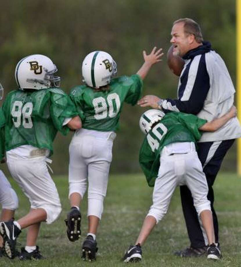 "Mark Adickes, an orthopedic surgeon and former professional football player, stays active on the gridiron as a ""trainer"" for his 11-year-old son's team. Photo: Carlos Antonio Rios, Chronicle"