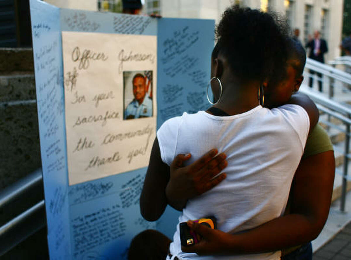 Amber, left, and Astin Johnson, daughters of slain HPD officer Rodney Johnson, embrace at a candlelight vigil Monday at Tranquillity Park. Members of the Nation of Islam and immigrant community leaders also attended the vigil.