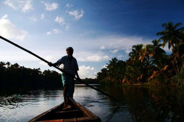 A boatman utilizes a bamboo pole to navigate one of many waterways near Kochi in the southern Indian state of Kerala.