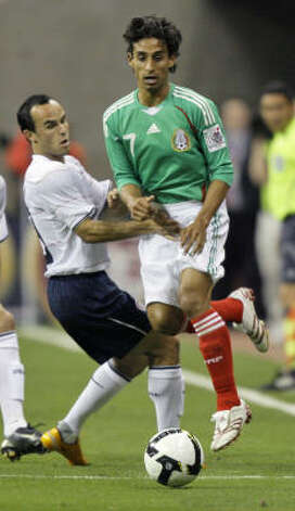 Mexico midfielder Fernando Arce (7) keeps the ball from United States forward Landon Donovan, left, during the first half. Photo: Associated Press