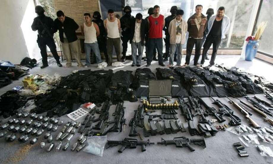 Men arrested by Mexican federal police stand behind weapons found Tuesday in a home in Mexico City. Photo: Gregory Bull, AP