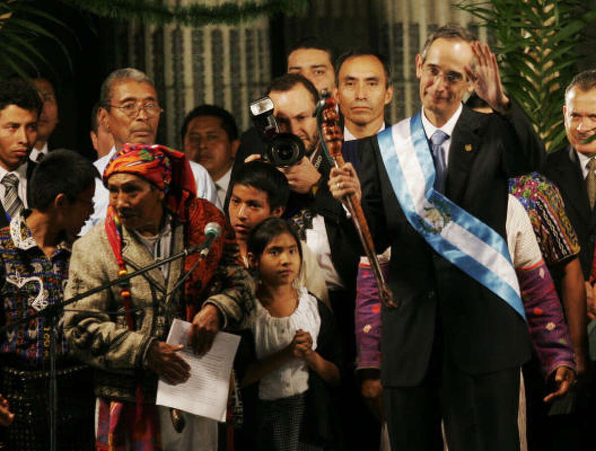 Guatemala's new president, Alvaro Colom, waves during a greeting ceremony Monday, holding a presidential cane given to him by representatives of the Maya people.