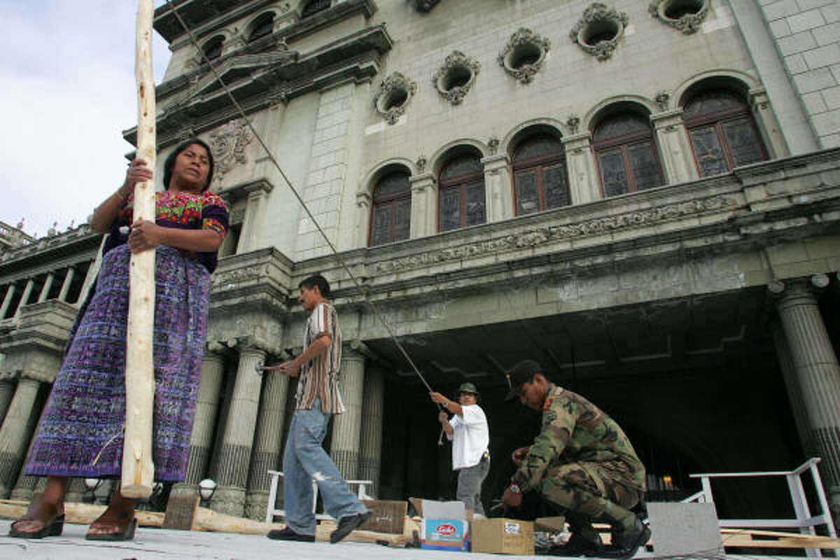 An Indian woman helps soldiers and workers in setting up a stage outside the National Palace of Culture in Guatemala City, in preparation for Monday's inauguration.