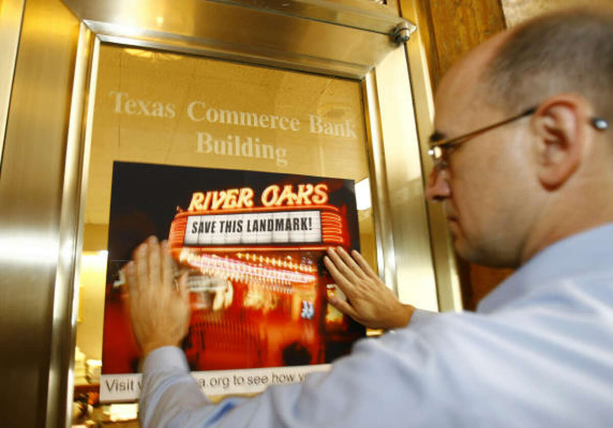 David Bush of the Greater Houston Preservation Alliance puts up a poster in support of saving the Landmark River Oaks Theatre at the organization's downtown office Thursday.