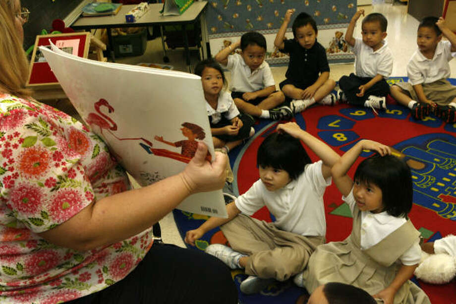 Cynthia and Cindy Nguyen read a book with their Park Place Elementary pre-K class and teacher Diane Krolczyk, who says she feels less rushed now than she did on the traditional half-day schedule. Photo: Carlos Antonio Rios, Houston Chronicle