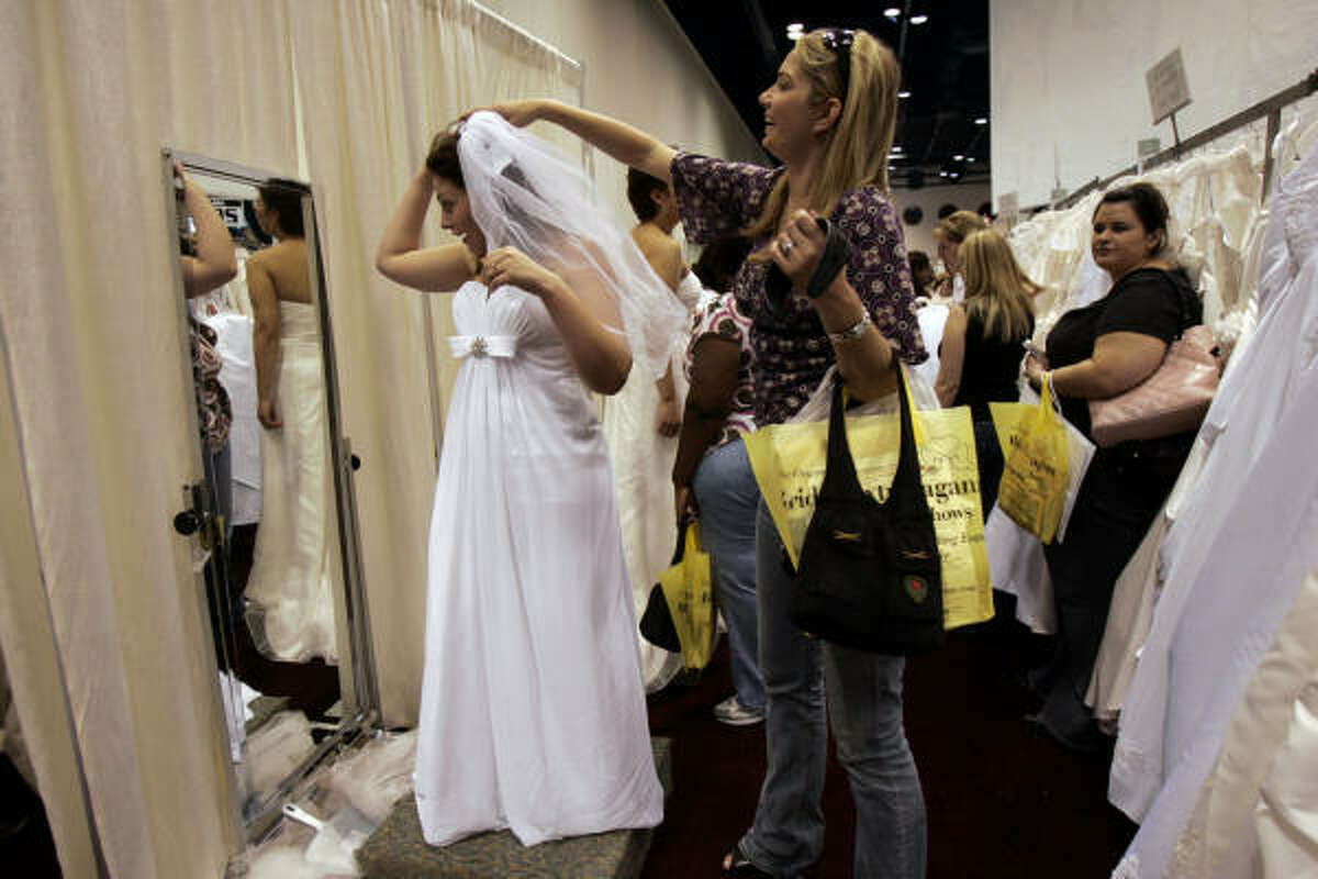 Future bride Cherice Braden, 24, is helped by her friend Lacey Hall, 22, as she tries on a wedding dress at the David's Bridal booth at the George R. Brown Convention Center on Saturday.