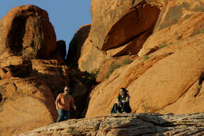 Michael Jasilewicz, left, and his friend Karen Urciuoli rest while hiking at Red Rock Canyon National Conservation Area in Nevada on May 5, 2006. Red Rock Canyon National Conservation Area for years has quietly lured rock climbers, petroglyph photographers, bicyclists, long-distance runners and lunch-toting hikers.