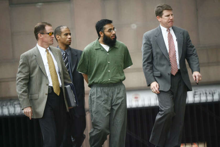 Shiraz Qazi, center, arrives at Houston's federal courthouse Wednesday accompanied by FBI agents. He is the cousin of Adnan Mirza, who is one of two men charged with aiding the Taliban. Photo: Steve Ueckert, Chronicle