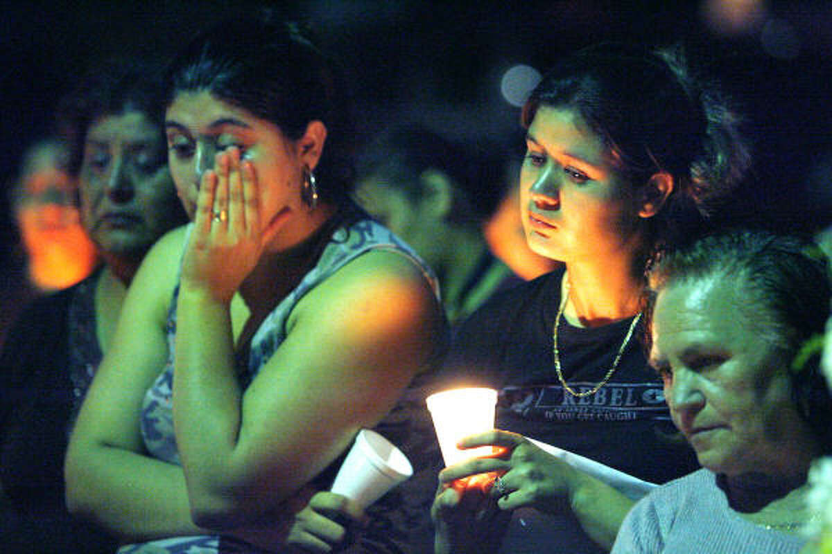 Rosa Rios, center, mother of 4-year-old Pedro Rios Jr., holds a candle during a vigil held by neighbors and friends. With her are Flor Borrego, left, aunt of Pedro Rios and Pedro's grandmother, Erminia Rios, right. Pedro died last week after two pit bulls attacked him while he was playing near his home.