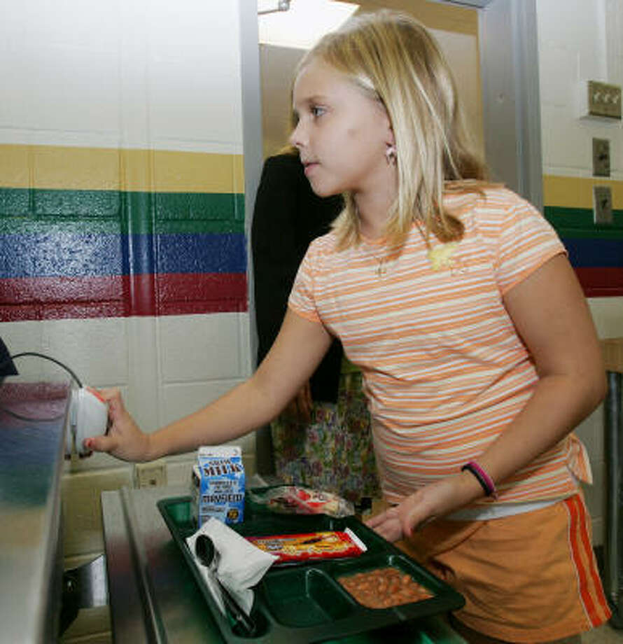 Hanna Jamsard, a fifth-grader at West End Elementary School in Rome, Ga., scans her finger to pay for her lunch. The school is using fingerprint scanners to allow students to pay for food without having to carry money to school. Photo: RIC FELD, AP