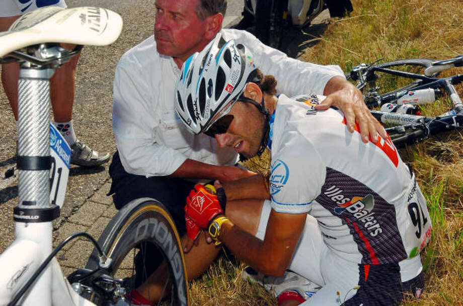 Alejandro Valverde of Spain is being helped by Tour de France chief doctor Gerard Porte, after he crashed  during the third stage on Tuesday. Photo: JEROME PREVOST, ASSOCIATED PRESS