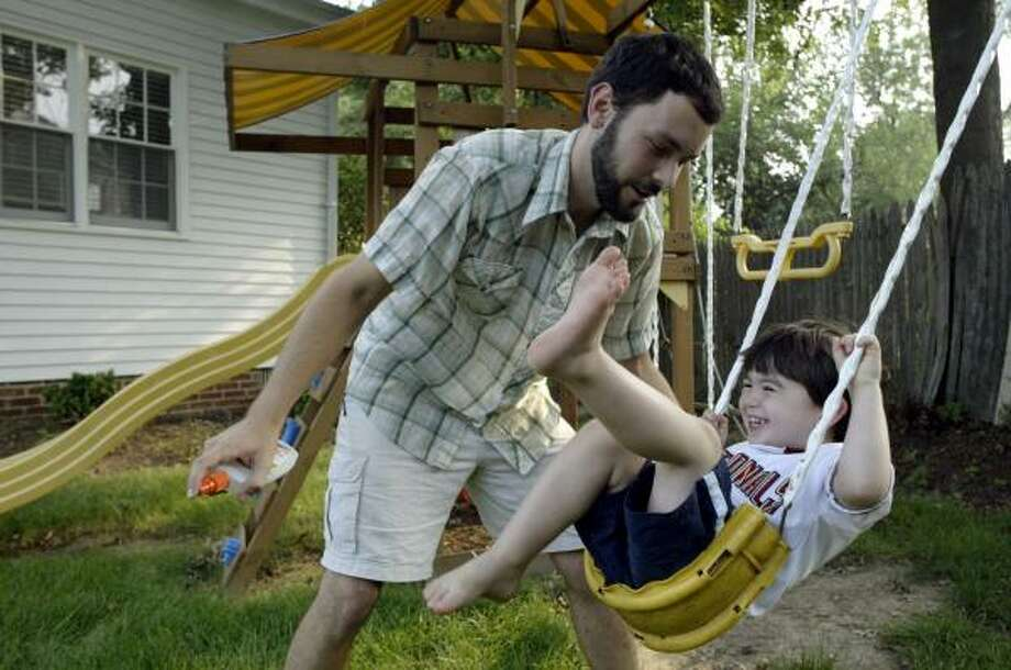 Adam Good, who works as a live-in male nanny for a couple in Alexandria, Va., tries to spray insect repellent on one of his charges, Jake Solomon, during playtime. Photo: KEVIN CLARK, Washington Post
