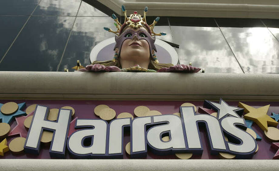 One of Harrah's trademark Mardi Gras clowns appears over the entrance to Harrah's Hotel and Casino in Las Vegas. The company has accepted a $17.1 billion buyout from Apollo Management Group and Texas Pacific Group. Photo: JOE CAVARETTA, AP File