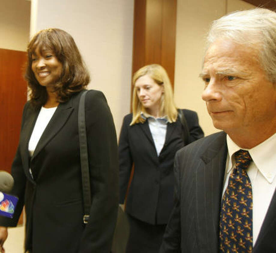 Former Texas Southern President Priscilla Slade, left, walks from the 338th District Court of the Harris County Justice Center along with her  attorney, Mike DeGeurin, far right. Photo: Billy Smith II, CHRONICLE