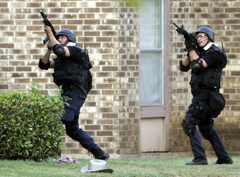 Members of a SWAT unit take aim at a second floor apartment window during a standoff in Midlothian on Sunday. Three police officers and a state trooper were shot and wounded during the ordeal that lasted more than eight hours. Photo: TONY GUTIERREZ, AP