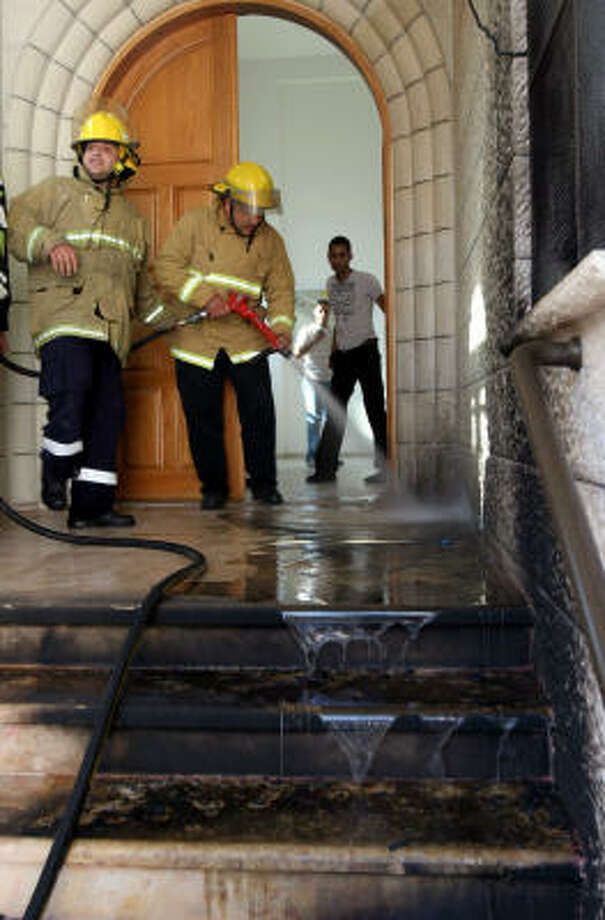 Firefighters douse flames Saturday at a Catholic church hit by a firebomb in the West Bank. Photo: NASSER ISHTAYEH, AP