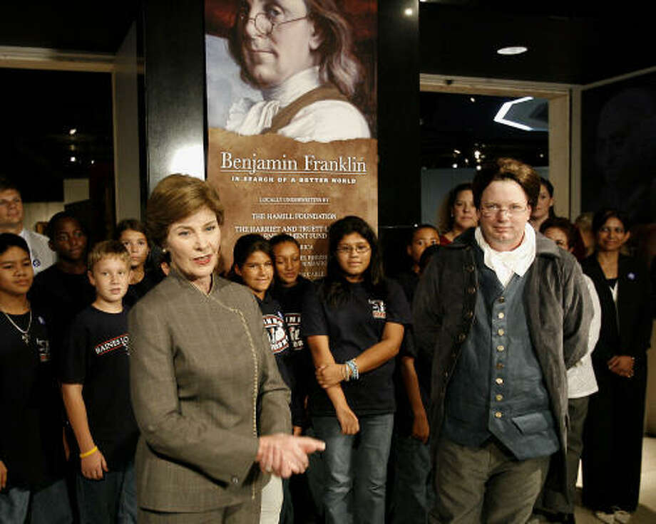 First lady Laura Bush and Ben Franklin, portrayed by David Temple, accompanied by students from Baines Middle School, speak with  the media after attending a Benjamin Franklin exhibition at the Houston Museum of Natural Sciences. Photo: BOB LEVEY, AP
